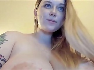 Sexy blonde with huge natural tits has fun in webcam showing her tattooed nipples.